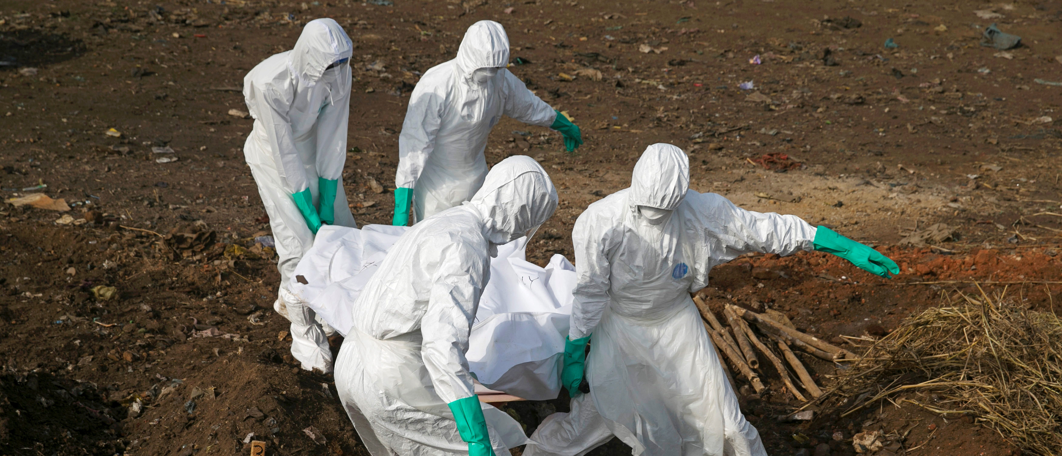 Health workers carry the body of a suspected Ebola victim for burial at a cemetery in Freetown, Sierra Leone, December 21, 2014. To match Special Report HEALTH-WHO/LEADER REUTERS/Baz Ratner/File Photo - S1BEUCYTJCAB