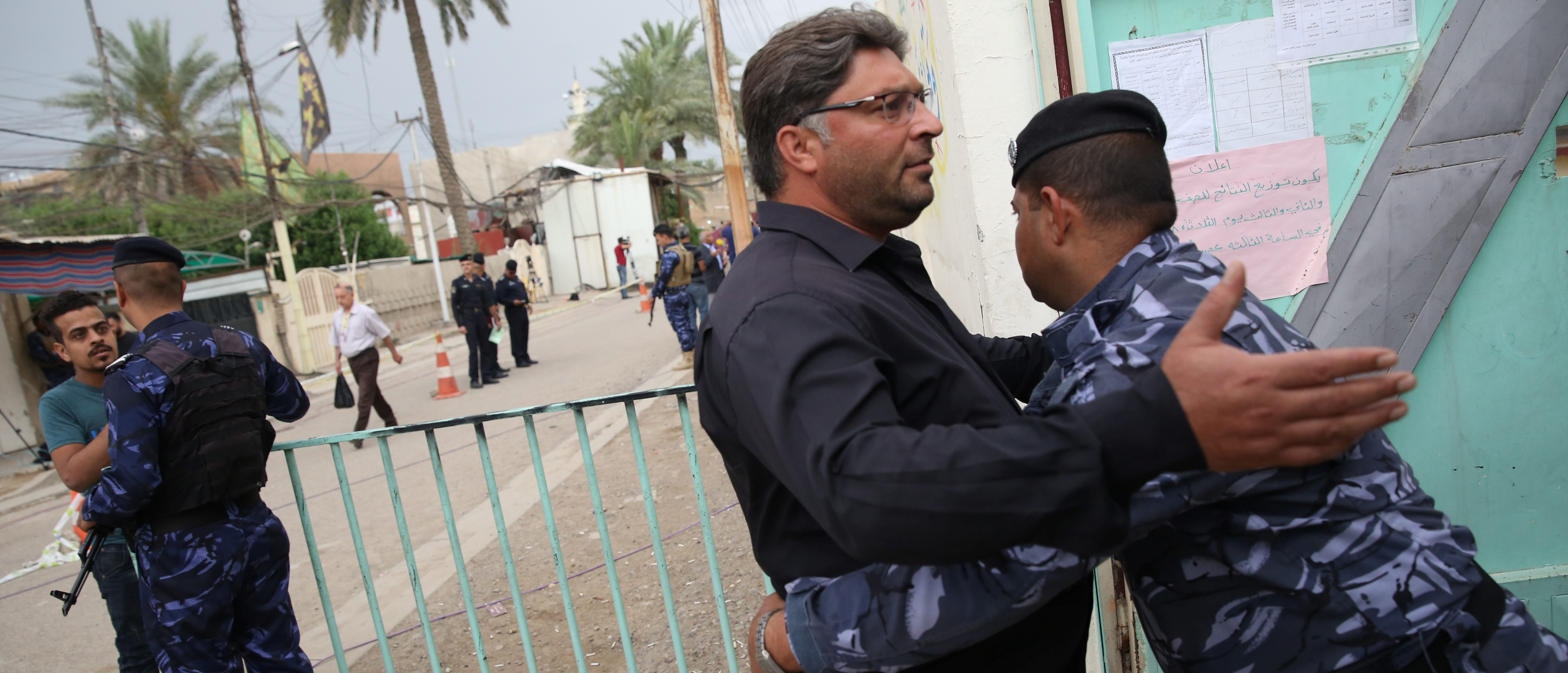 Iraqi security forces check people before entering a polling station during the parliamentary election in Baghdad, Iraq May 12, 2018. REUTERS/Abdullah Dhiaa al-Deen - RC1C40318DF0