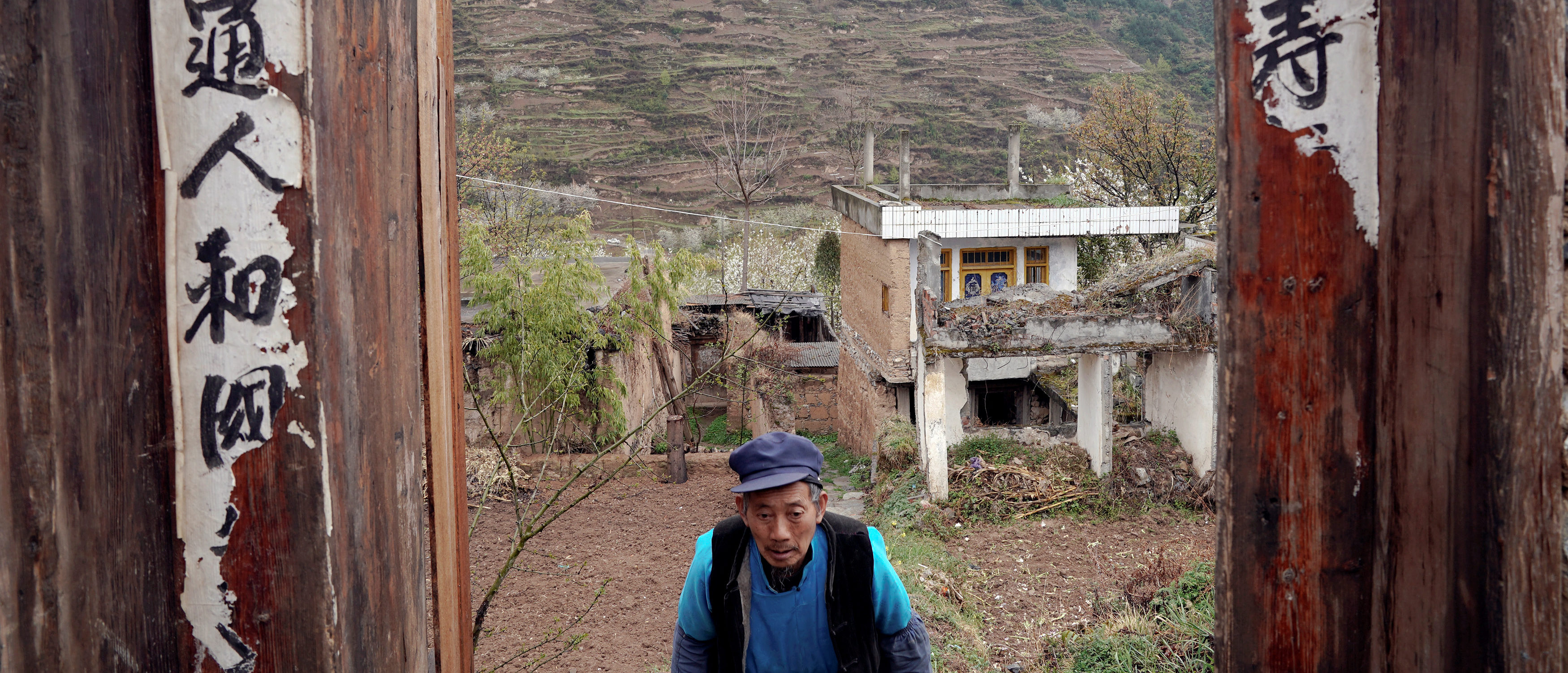 Surviving villager Ma Qingan walks through doors after leaving his old house at a minority village which was badly damaged in the 2008 Sichuan earthquake in Wenchuan county, Sichuan province, China, April 5, 2018. REUTERS/Jason Lee