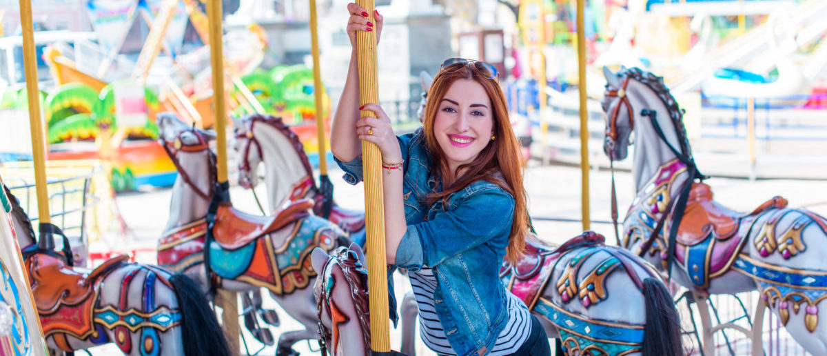 Adult girl has fun on the carousel and has a good time. The concept of fun in the city Shutterstock/ T.Den