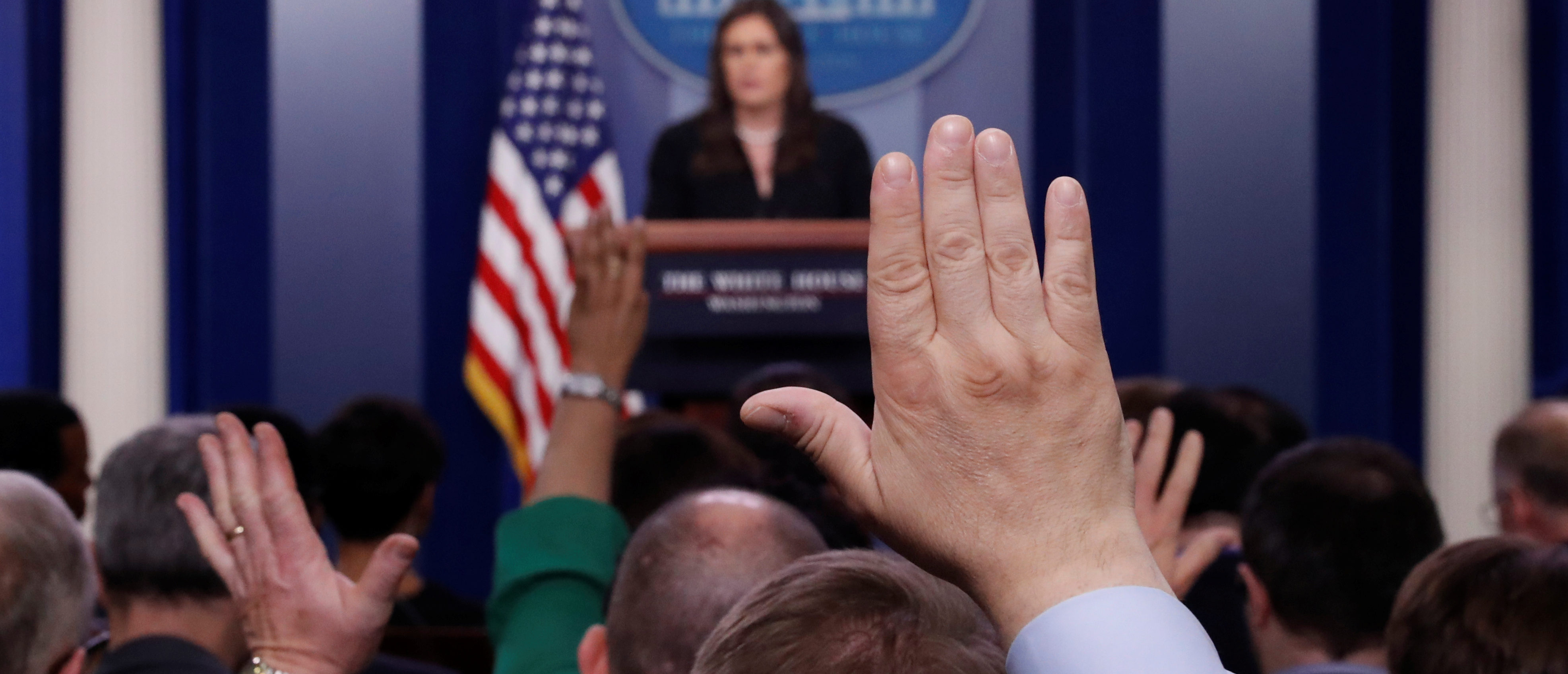 Members of the news media raise their hands to ask questions of White House Press Secretary Sarah Huckabee Sanders during a daily briefing at the White House in Washington, March 12, 2018. REUTERS/Leah Millis
