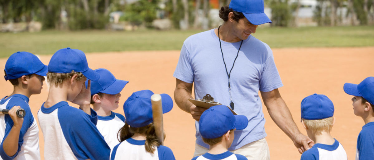 Youth baseball team and coach on pitch (SHUTTERSTOCK: By Air Images)