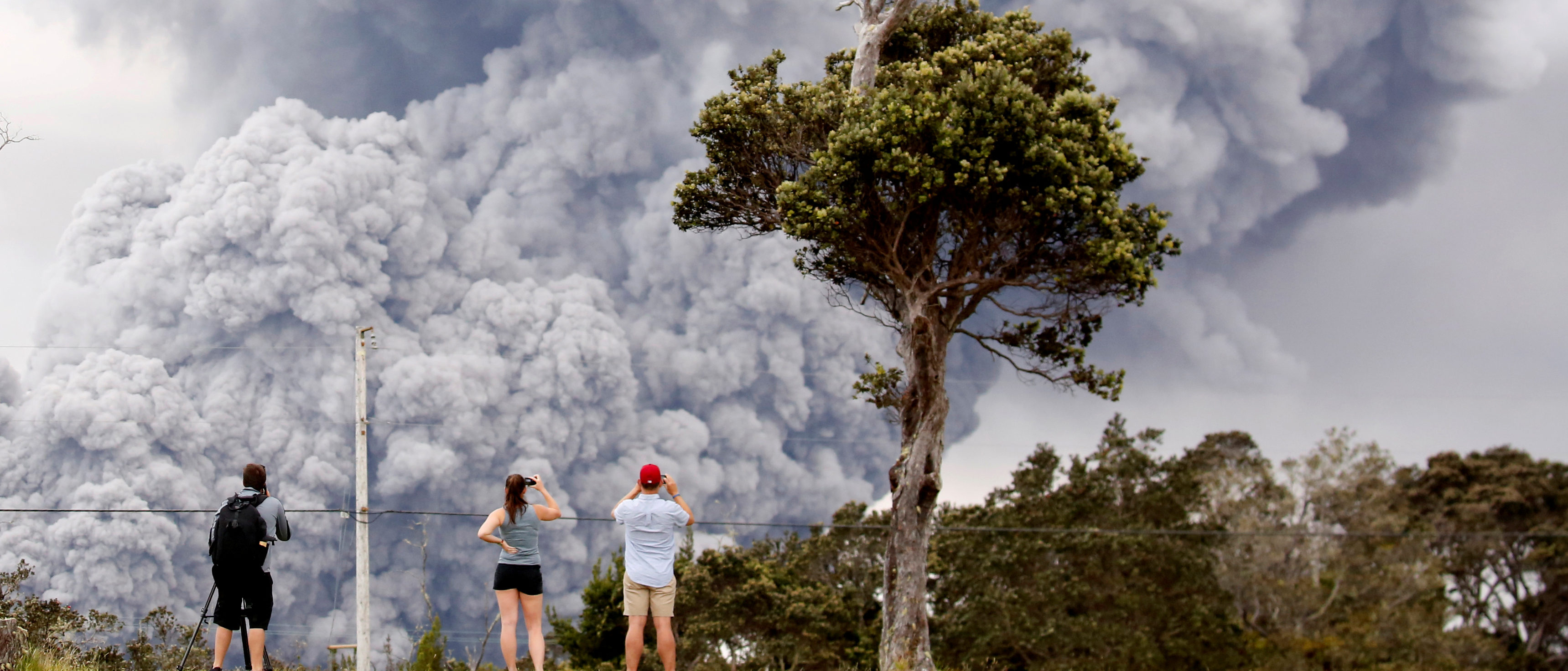 People watch as ash erupts from the Halemaumau crater near the community of Volcano during ongoing eruptions of the Kilauea Volcano in Hawaii, May 15, 2018. REUTERS/Terray Sylvester