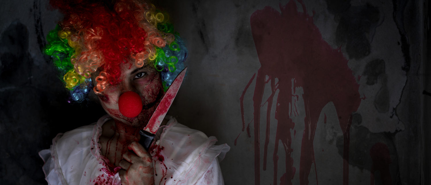 Ghost woman clown or zombie crown holding knife for kill with blood violence in house of ruin, nightmare, horror of scary fear on hell is monster devil in halloween festival, copy space the right. (Shutterstock/Zodiacphoto) | Clown-Clad Woman Stabs Lover During Sex