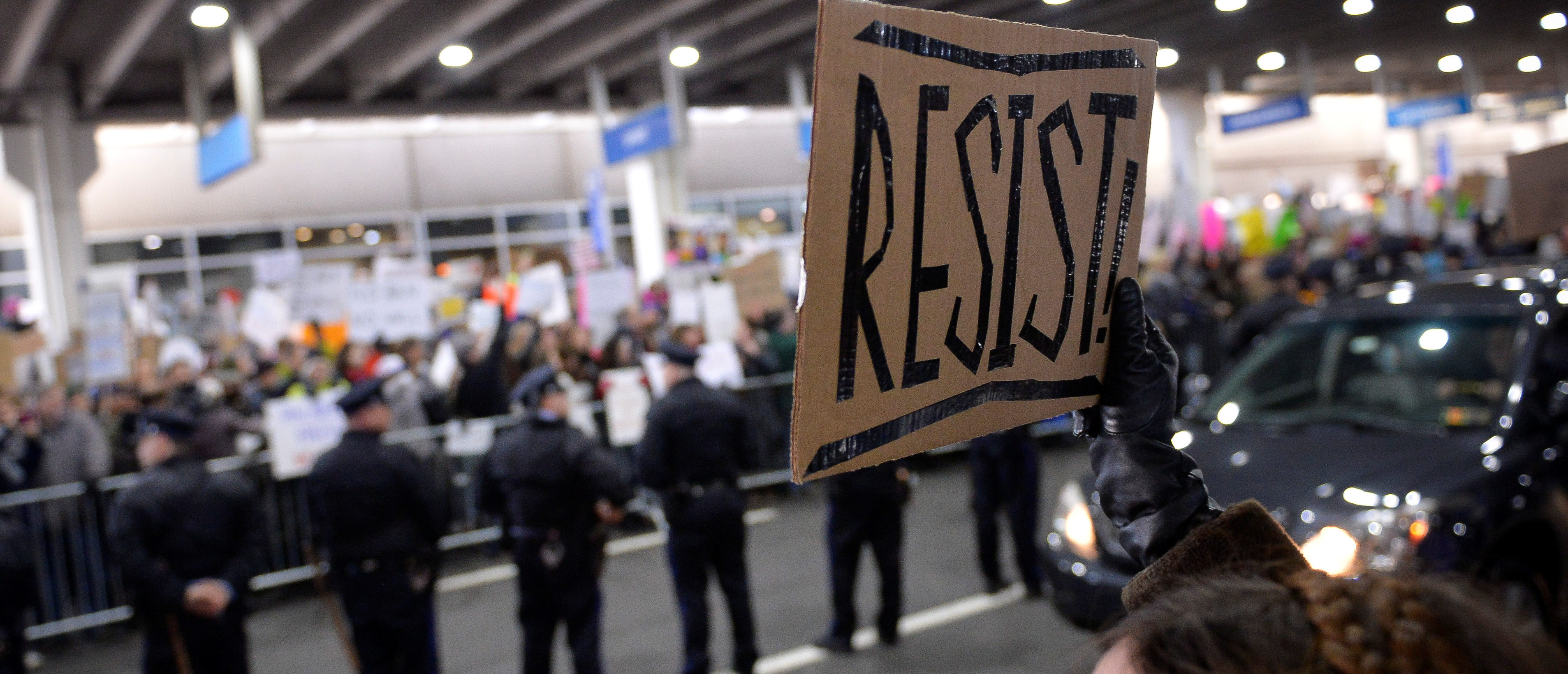 """A demonstrator holds a """"resist"""" sign during anti-Donald Trump travel ban protests outside Philadelphia International Airport in Philadelphia, Pennsylvania, U.S., January 29, 2017. REUTERS/Charles Mostoller - RC1C22B44C50"""