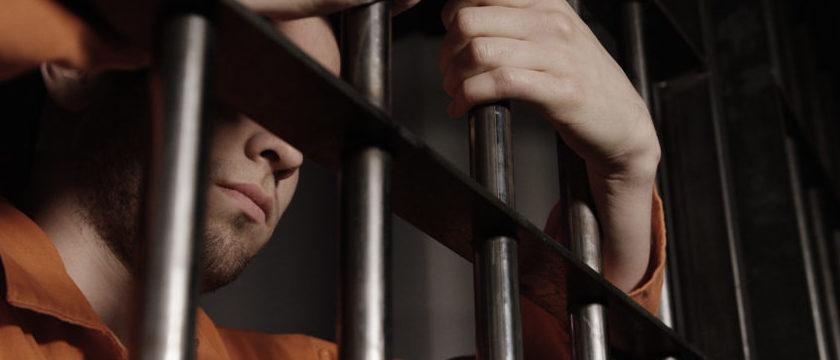 Man in jail behind bars - Caucasian young gang member Skyward Kick Productions/Shutterstock