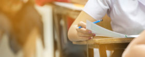 Blur abstract background of examination room with undergraduate students inside. student sitting on row chair doing final exam in classroom. (Shutterstock)