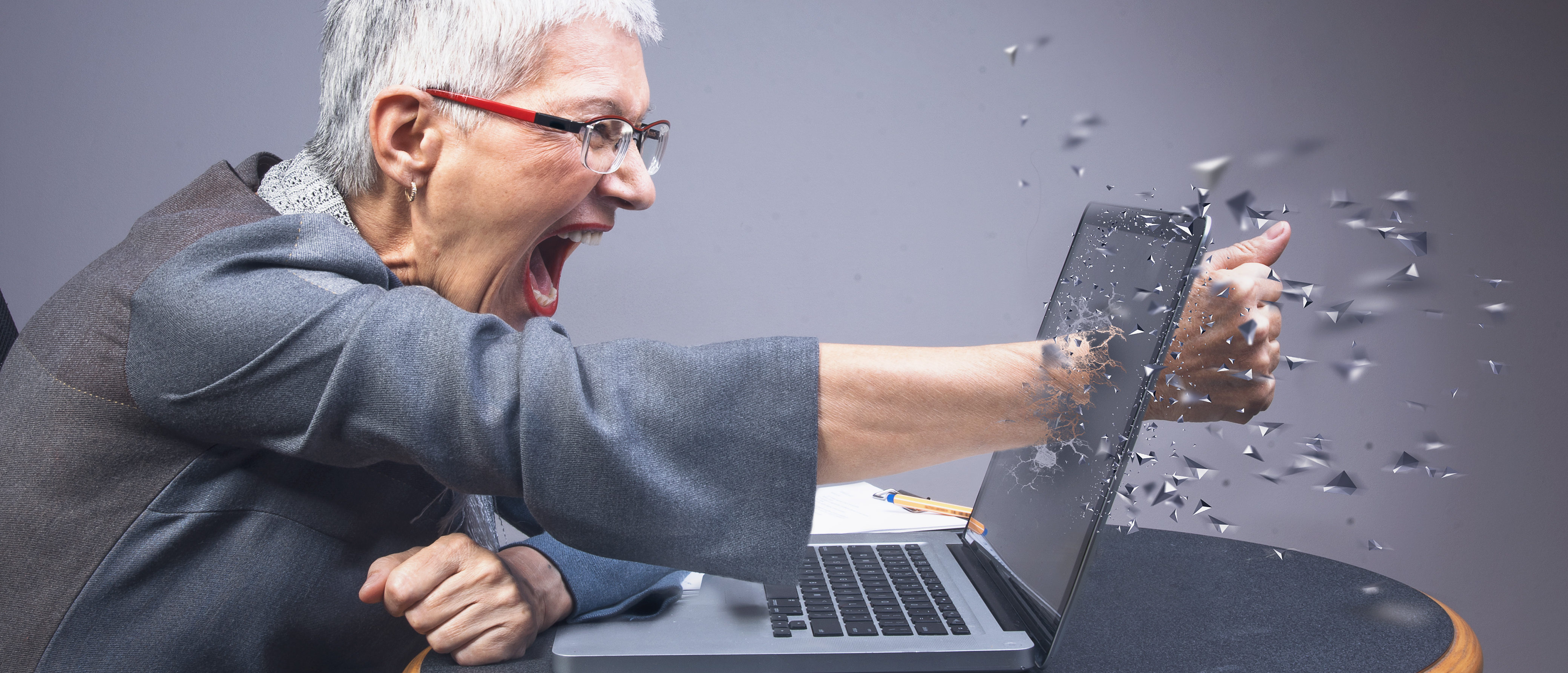 Elderly woman takes anger out on laptop. [Shutterstock, by TeodorLazarev]