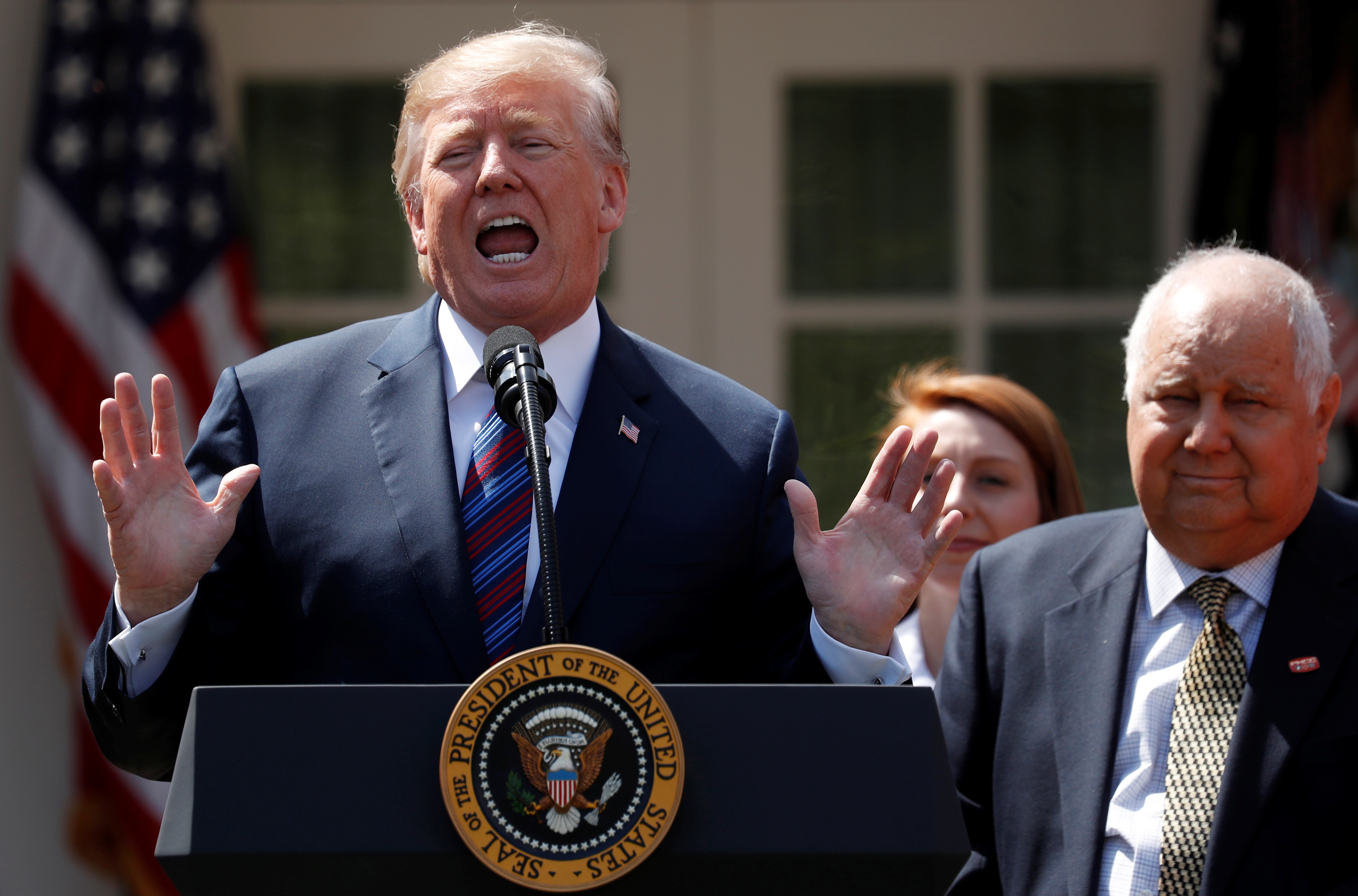 U.S. President Donald Trump gives remarks on tax cuts for American workers as Richard Kerzetski of Universal Plumbing, North Las Vegas, Nevada, listens during an event in the White House Rose Garden in Washington, U.S., April 12, 2018. REUTERS/Kevin Lamarque/File Photo - RC1E3CD3EA20