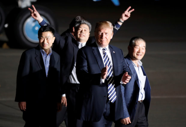 The three Americans formerly held hostage in North Korea gesture next to U.S.President Donald Trump, upon their arrival at Joint Base Andrews, Maryland, U.S., May 10, 2018. REUTERS/Jim Bourg - RC1FDB2A7BD0
