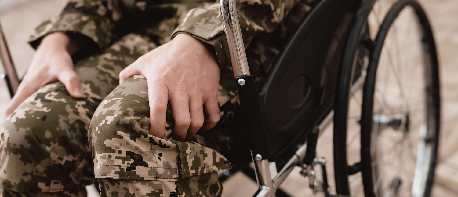 Veteran in wheelchair returned from army. Close-up photo veteran in a wheelchair. Wheelchairs and legs in military uniform. (Shutterstock/VGstockstudio) | Jim Smith Federal Vet Contracts Faulted