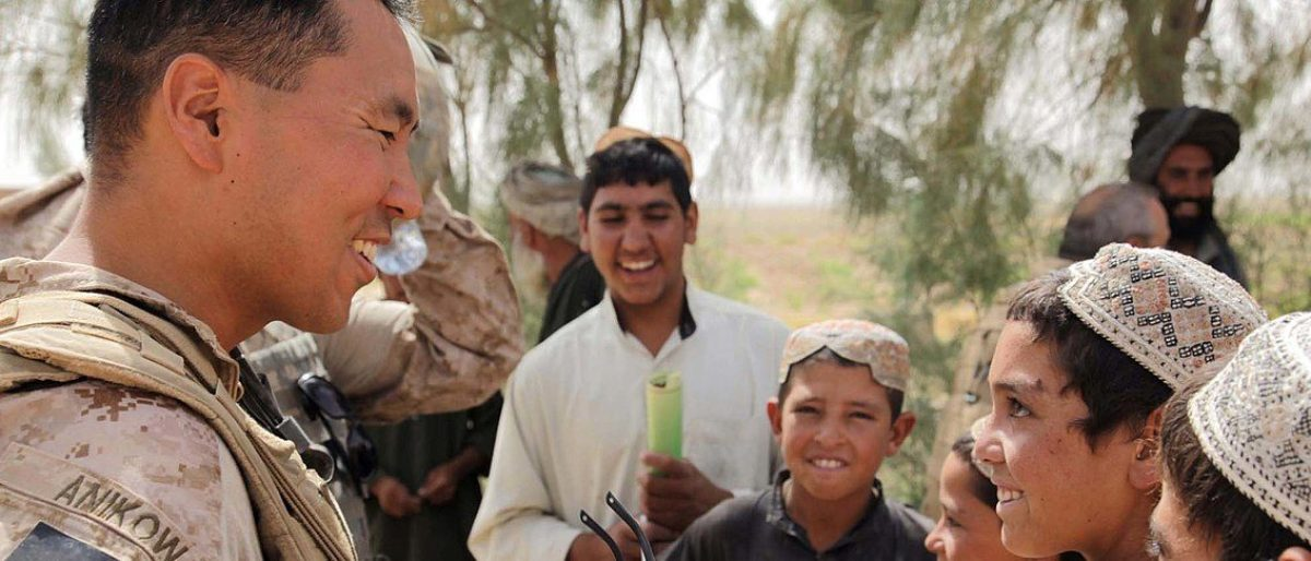 Maj. George Anikow, Civil Affairs detachment executive officer with Regimental Combat Team 3, jokes with local children during a patrol in Helmand Province, Afghanistan, Aug. 18, 2009. Sgt. Pete Thibodeau