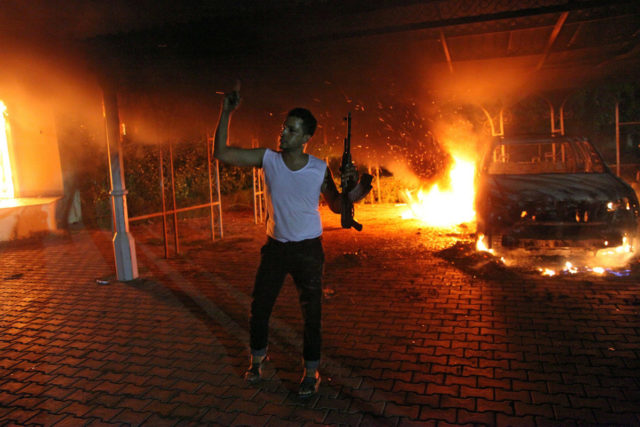 An armed man waves his rifle as buildings and cars are engulfed in flames after being set on fire inside the US consulate compound in Benghazi late on September 11, 2012. An armed mob protesting over a film they said offended Islam, attacked the US consulate in Benghazi and set fire to the building, killing one American, witnesses and officials said. (Photo credit should read STR/AFP/GettyImages)