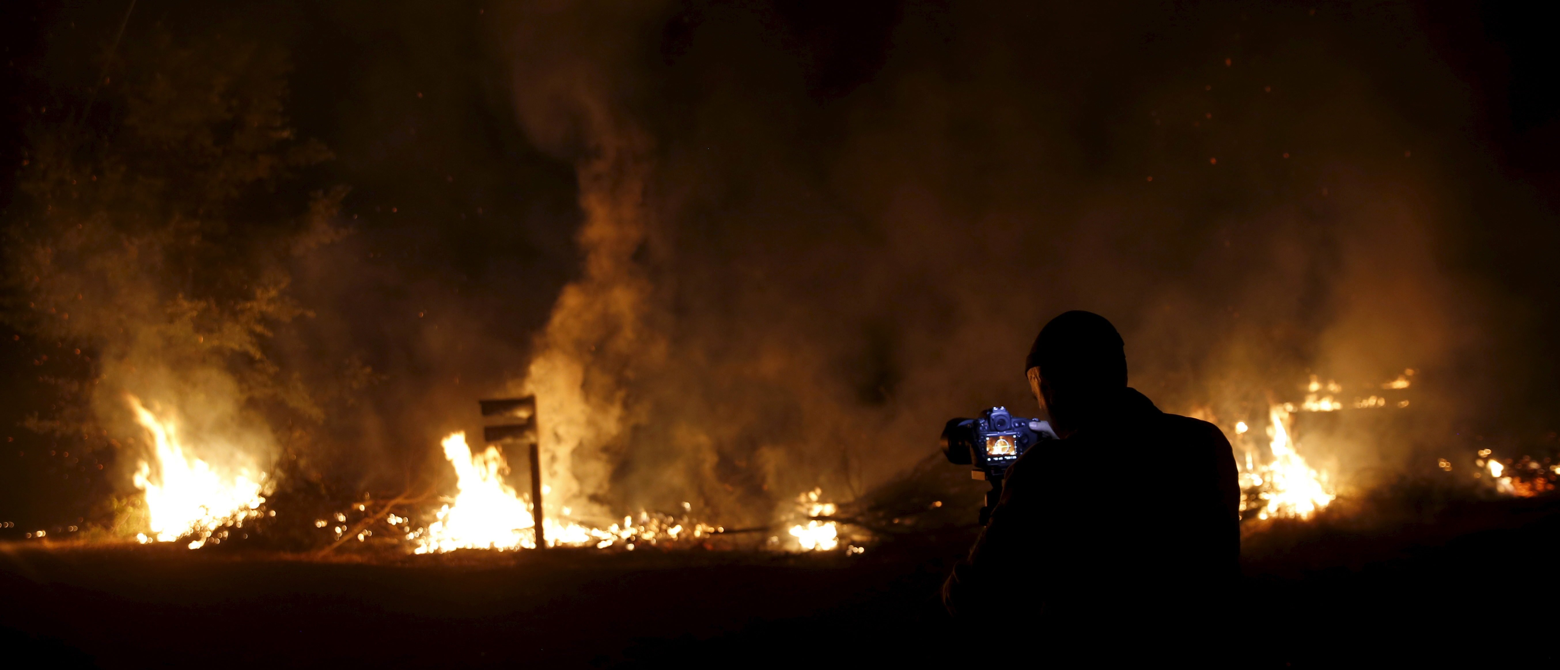 A photographer takes photographs of flames at the Jerusalem Fire in Lake County, California August 12, 2015. A wildfire burning in northern California grew rapidly on Tuesday near another massive blaze that has destroyed dozens of buildings, forcing some residents to evacuate their homes for the second time in as many weeks.The so-called Jerusalem Fire, sparked on Sunday, has spread across 14,000 acres (5,665 hectares) and was burning aggressively through drought-parched vegetation north of Napa Valley wine country, the California Department of Forestry and Fire Protection (Cal Fire) said. REUTERS/Robert Galbraith - GF10000172428