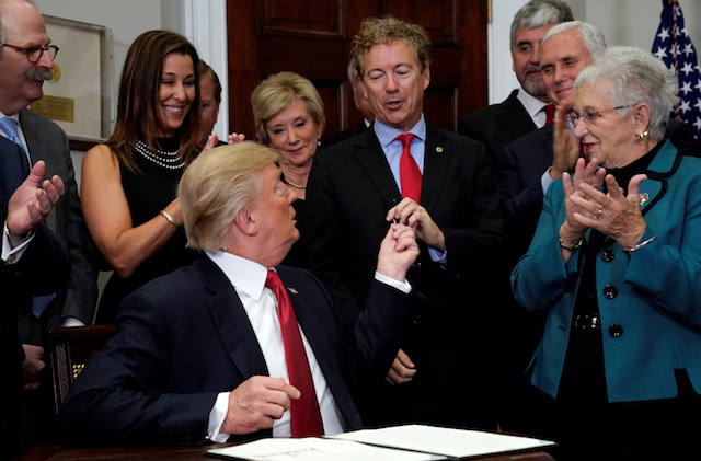 U.S. Senator Rand Paul (R-KY) is given the pen after U.S. President Donald Trump signed an executive order to make it easier for Americans to buy bare-bones health insurance plans and circumvent Obamacare rules at the White House in Washington, U.S., October 12, 2017. REUTERS/Kevin Lamarque