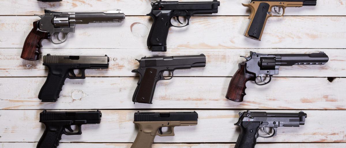 Guns on a white wooden background. (Shutterstock/Fabrika Simf)