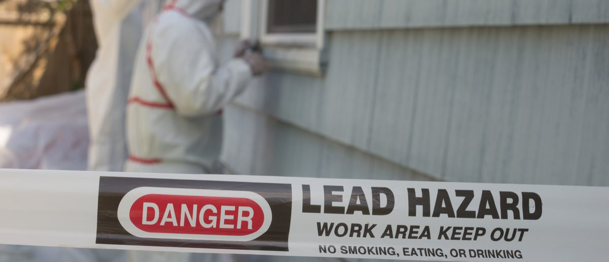 Two house painters in hazmat suits remove lead paint from an old house. (Shutterstock/Jamie Hooper)