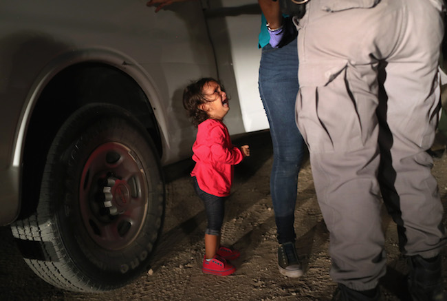 A two-year-old Honduran child cries as her mother is searched and detained near the U.S.-Mexico border on June 12, 2018 in McAllen, Texas. (Photo by John Moore/Getty Images)