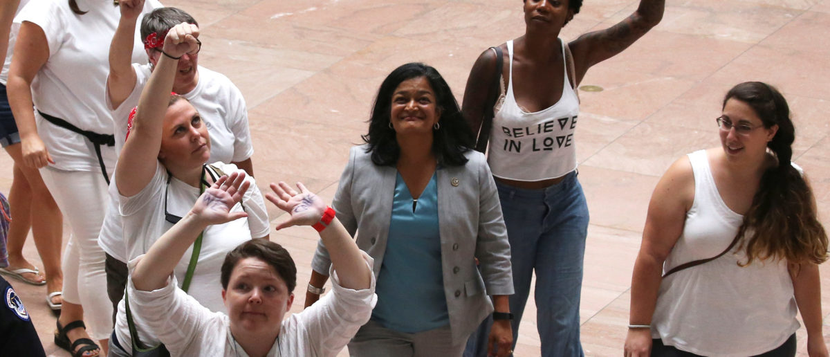 """U.S. Representative Pramila Jayapal (D-WA) (3rd R) walks to be arrested as she joined demonstrators calling for """"an end to family detention"""" and in opposition to the immigration policies of the Trump administration, at the Hart Senate Office Building on Capitol Hill in Washington, U.S. June 28, 2018. (REUTERS/Jonathan Ernst)"""