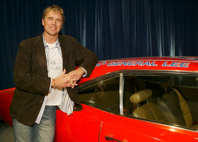 "Actor John Schneider poses with the ""General Lee"" car from ""The Dukes of Hazard"" televison show he starred in during the ""Warner Brothers Television and Warner Home Video Celebrate 50 Years of Quality TV"" party at Warner Brothers Studio in Burbank, California, January 20, 2005. REUTERS/Lee Celano SSM - RP5DRIESGAAA"