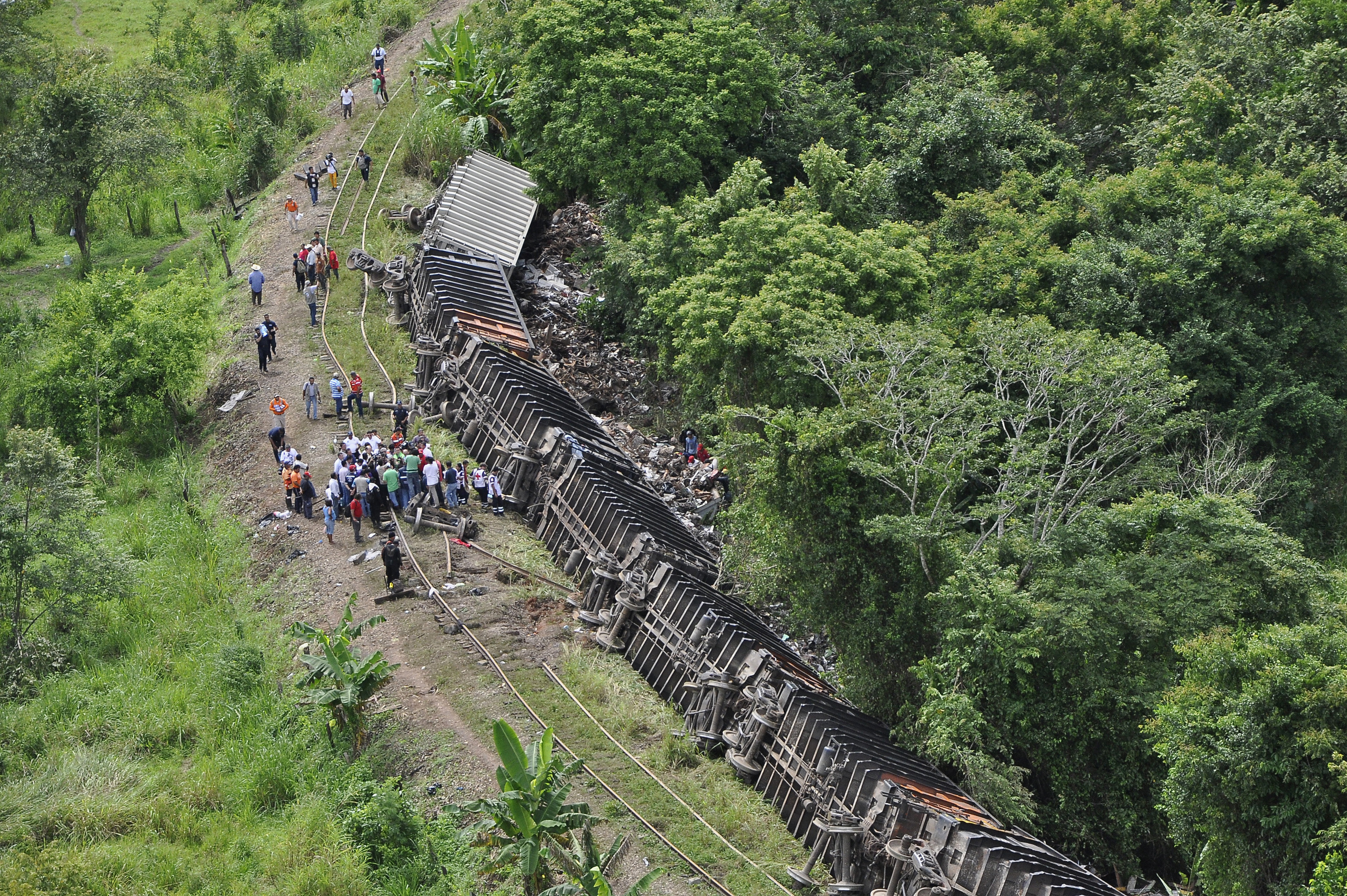 """Railroad workers and police investigators stand near the overturned carriages of a derailed train in Huimanguillo, in the Mexican state of Tabasco August 25, 2013. At least six people were killed when a cargo train nicknamed """"La Bestia,"""" or """"The Beast,"""" on which would-be migrants hitch rides toward the U.S. border, derailed in a remote area of southern Mexico on Sunday, state officials said. REUTERS/Luis Manuel Lopez"""