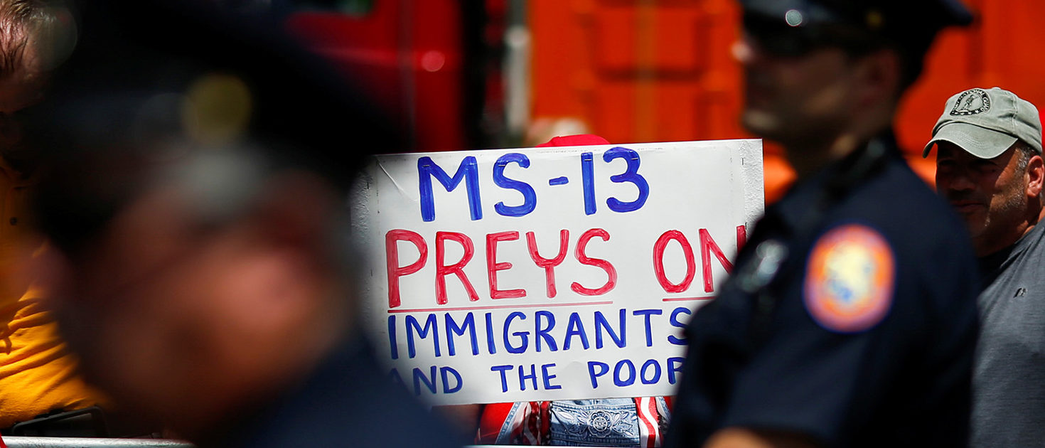 U.S. president Trump supporters hold placards against MS-13 as New York Police stand guard at the street during a forum about Central American-based Mara Salvatrucha (MS-13) gang organization at the Morrelly Homeland Security Center in Bethpage, New York, U.S., May 23, 2018. REUTERS/Eduardo Munoz