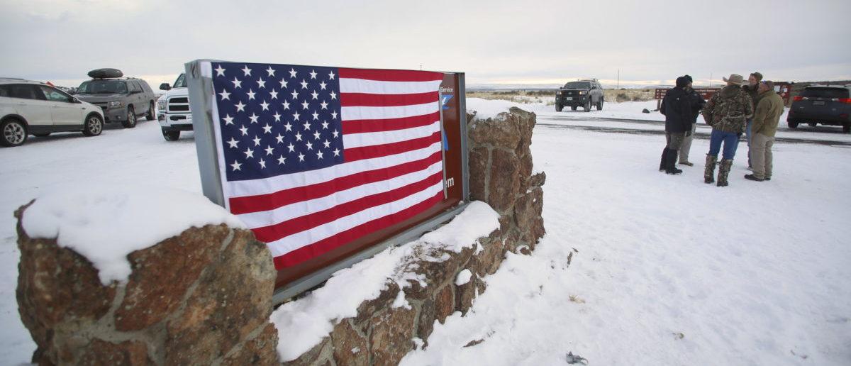 A U.S. flag covers a sign at the entrance of the Malheur National Wildlife Refuge near Burns, Oregon, U.S. January 3, 2016. REUTERS/Jim Urquhart