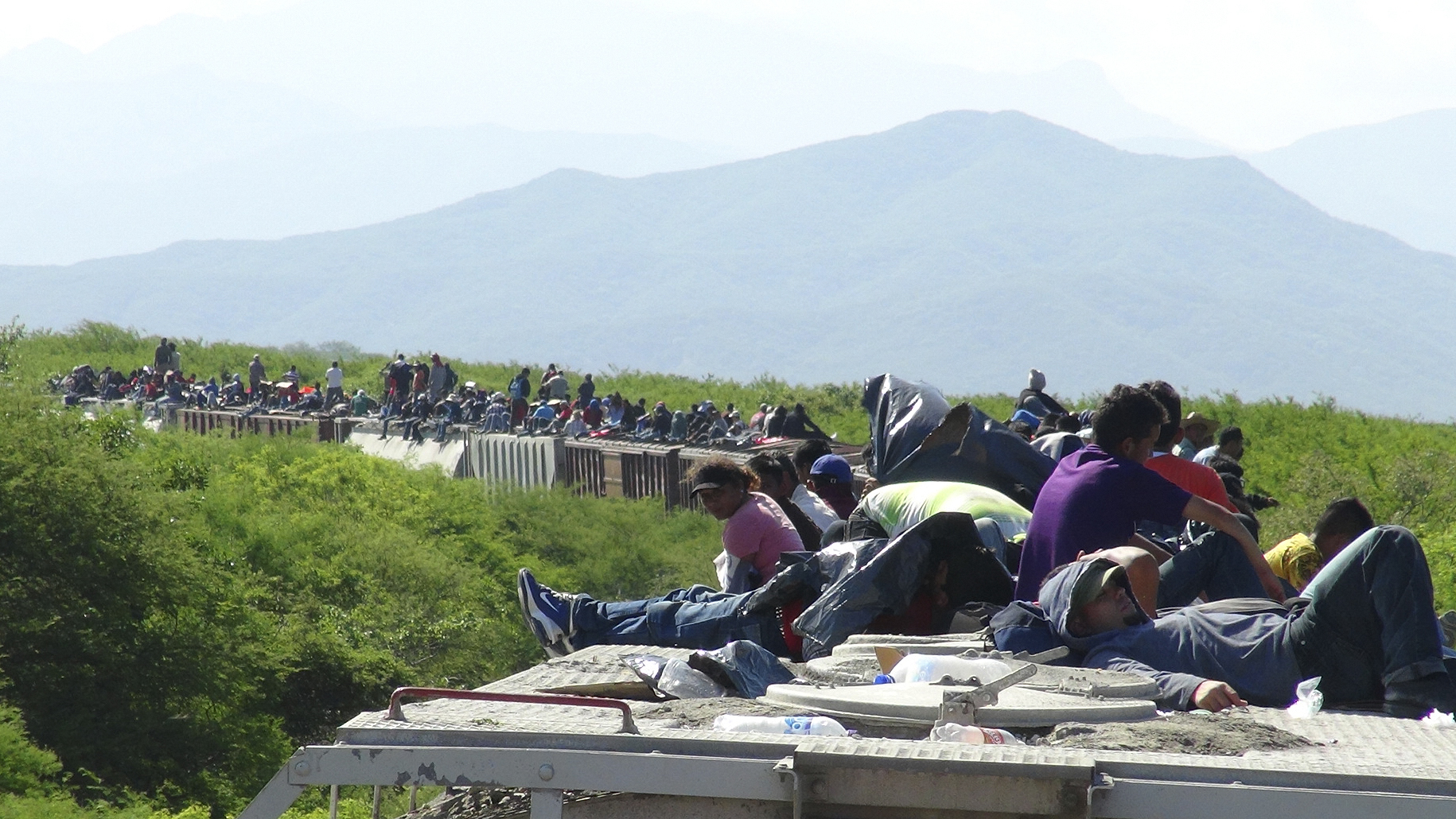People hoping to reach the U.S. ride atop the wagon of a freight train, known as La Bestia (The Beast) in Ixtepec, in the Mexican state of Oaxaca June 18, 2014. Thousands of young people are hoping to reach the U.S. from their impoverished and violent homes in Central America. In the eight months ended June 15, the U.S. has detained about 52,000 children at the Mexican border, double the figure the year earlier. There's no telling how many have gotten through. Picture taken June 18, 2014. To match FEATURE USA-IMMIGRATION/MEXICO REUTERS/Jose de Jesus Cortes