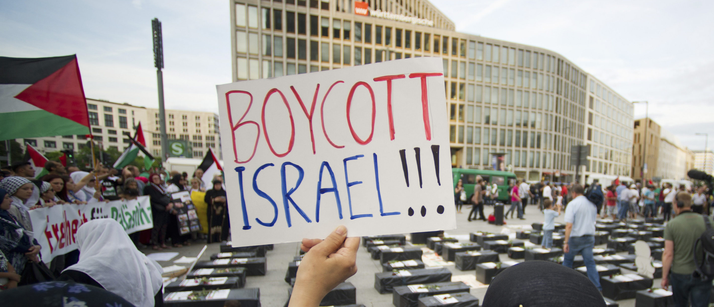 "A woman holds a sign which reads ""Boycott Israel"" in front of symbolic coffins while attending a demonstration supporting Palestine, in Berlin August 1, 2014. Israel launched its Gaza offensive on July 8 in response to a surge of rocket attacks by Gaza's dominant Hamas Islamists. Hamas said that Palestinians would continue confronting Israel until its blockade on Gaza was lifted. REUTERS/Steffi Loos (GERMANY - Tags: POLITICS CIVIL UNREST) - GM1EA8206QF02"