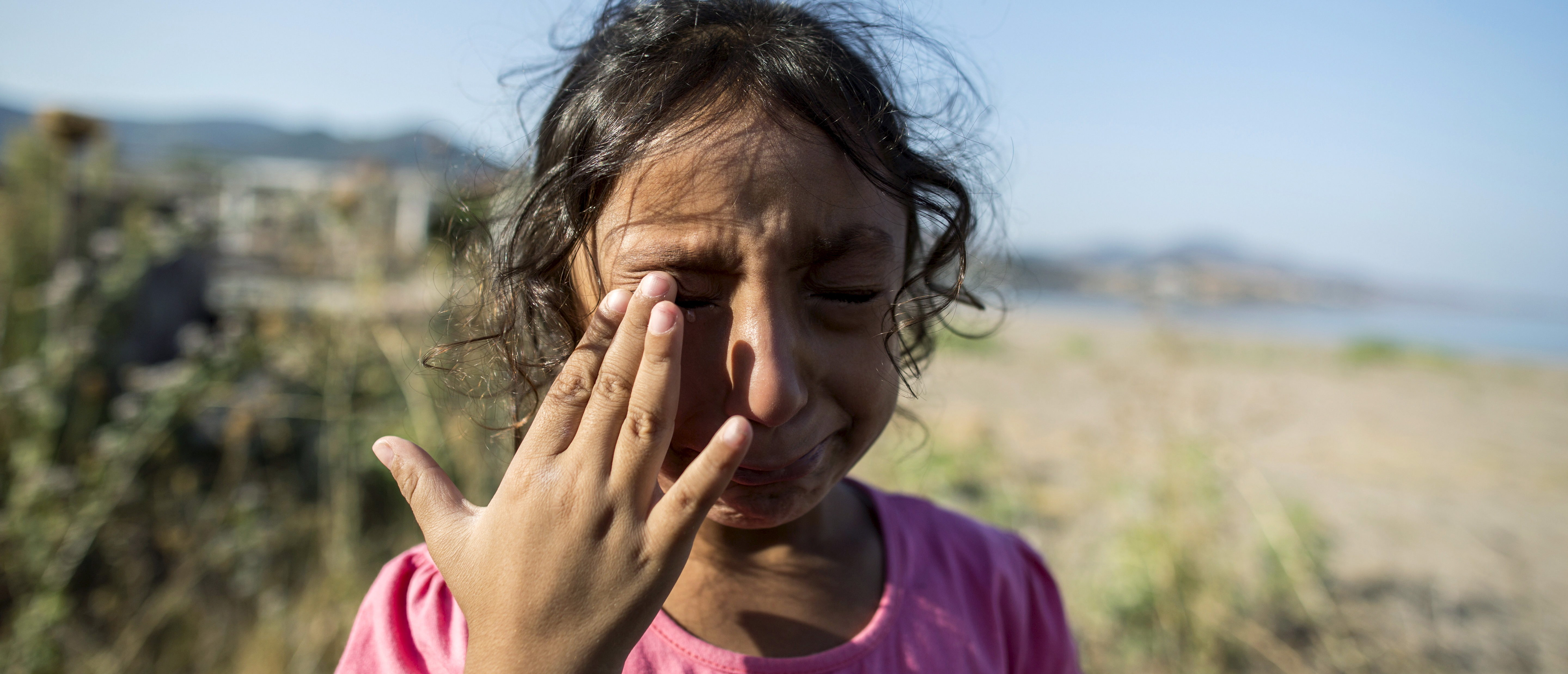 Yasmine, a 6-year-old migrant from Deir Al Zour in war-torn Syria, cries at the beach after arriving on the Greek island of Lesbos September 11, 2015. Yasmine said that the men who brought her family across the narrow sea between Bodrum in Turkey and this Greek tourist island threw away the dress her grandmother gave her. The crossing from Turkey and the eventual trip to Athens is only the beginning for Yasmine and other families. Ahead lies a trek north through Greece, up via Macedonia and Serbia to Hungary and on to Austria, Germany and more industrialised countries. Picture taken September 11, 2015. REUTERS/Zohra Bensemra - GF10000206087