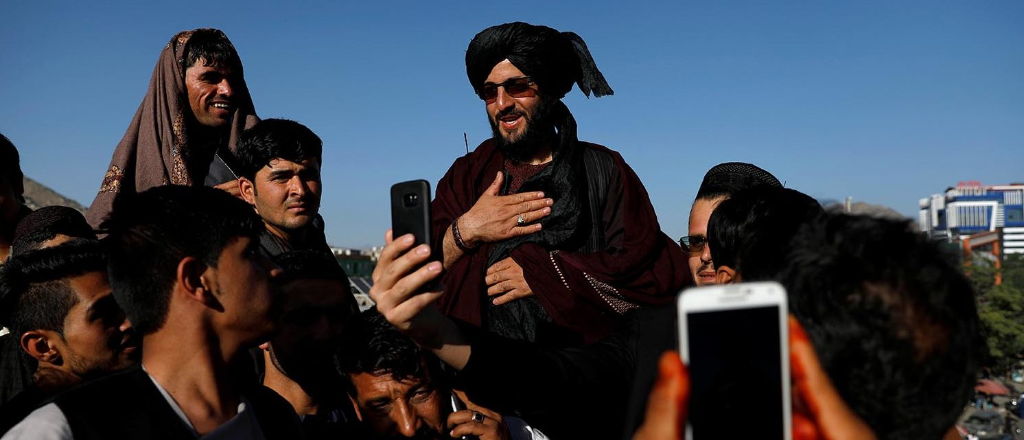 People take selfies with a Taliban in Kabul, Afghanistan June 16, 2018. REUTERS/Mohammad Ismail