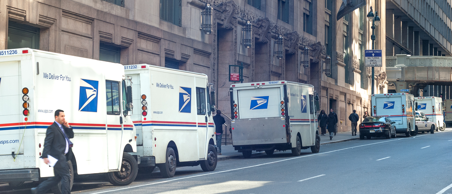 USPS delivery trucks lined up by James A. Farley Post Office landmark building on March 25, 2008 in Midtown Manhattan, New York City, USA (Shutterstock/Natalia Bratslavsky)