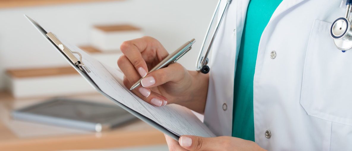 Close-up view of female doctor hands filling patient registration form. Healthcare and medical concept. (Shutterstock_349234109)