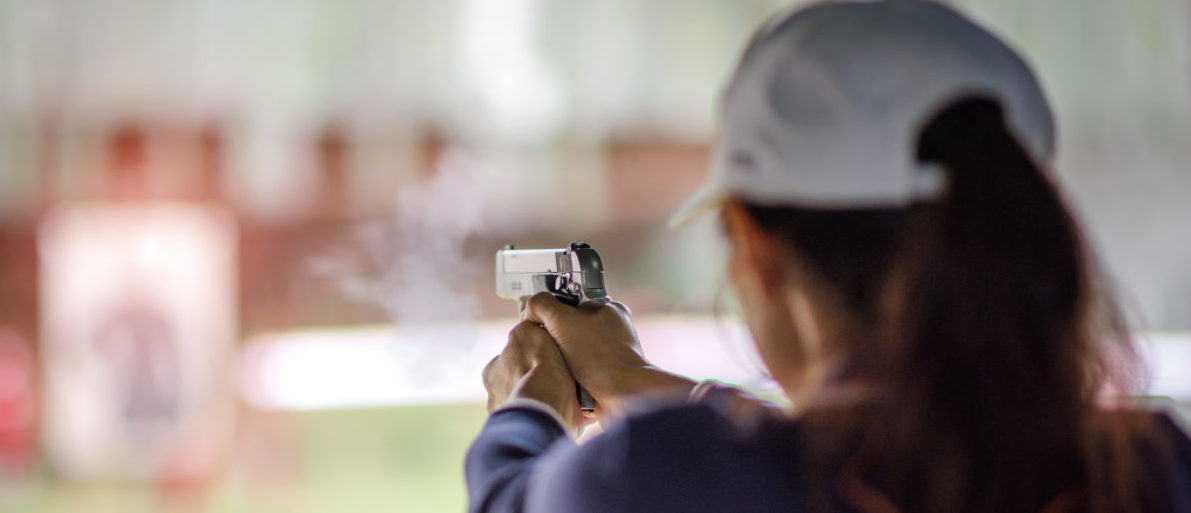 gun holding in hand of woman in practice shooting in martial arts for self defense in an emergency case Shutterstock/Iam_Anupong