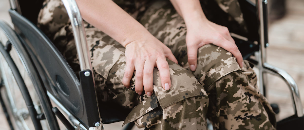 Woman veteran in wheelchair returned from army. Close-up photo veteran woman in a wheelchair. Wheelchairs and legs in military uniform. (Shutterstock/VGstockstudio)