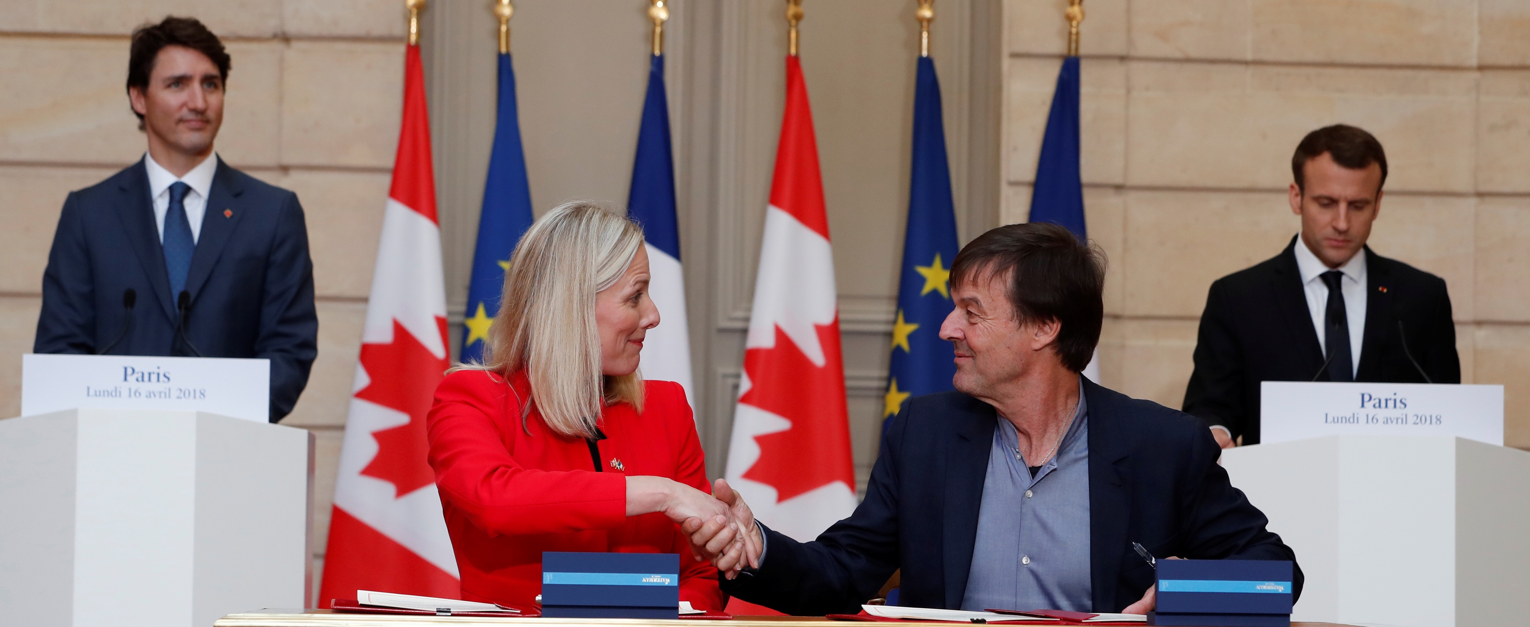 French President Emmanuel Macron (R) and Canadian Prime Minister Justin Trudeau (L) appaud as French minister of Ecology Nicolas Hulot (2ndR) and Canadian counterpart Catherine McKenna (2ndL) sign a ecology treaty at the Elysee Palace in Paris, France, April 16, 2018. Ian Langsdon/Pool via Reuters - RC19F7E98420
