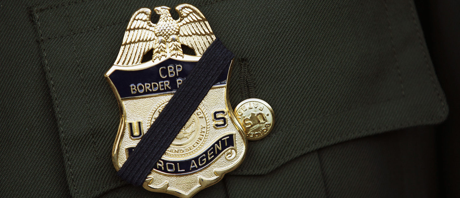 A U.S. Border Patrol agent wears a black band over his badge during a memorial service for slain comrade Brian Terry on January 21, 2011 in Tucson, Arizona. Agent Terry was killed during a December14 shootout with suspected bandits near the U.S.-Mexico Border. Thousands of Border Patrol agents and fellow law enforcement officers from across Arizona turned out for the memorial service held at Kino baseball stadium in Tucson. With U.S. agents tracking drug smugglers and illegal immigrants all along the border, the region is one of the most militarized areas of the United States. (Photo by John Moore/Getty Images)