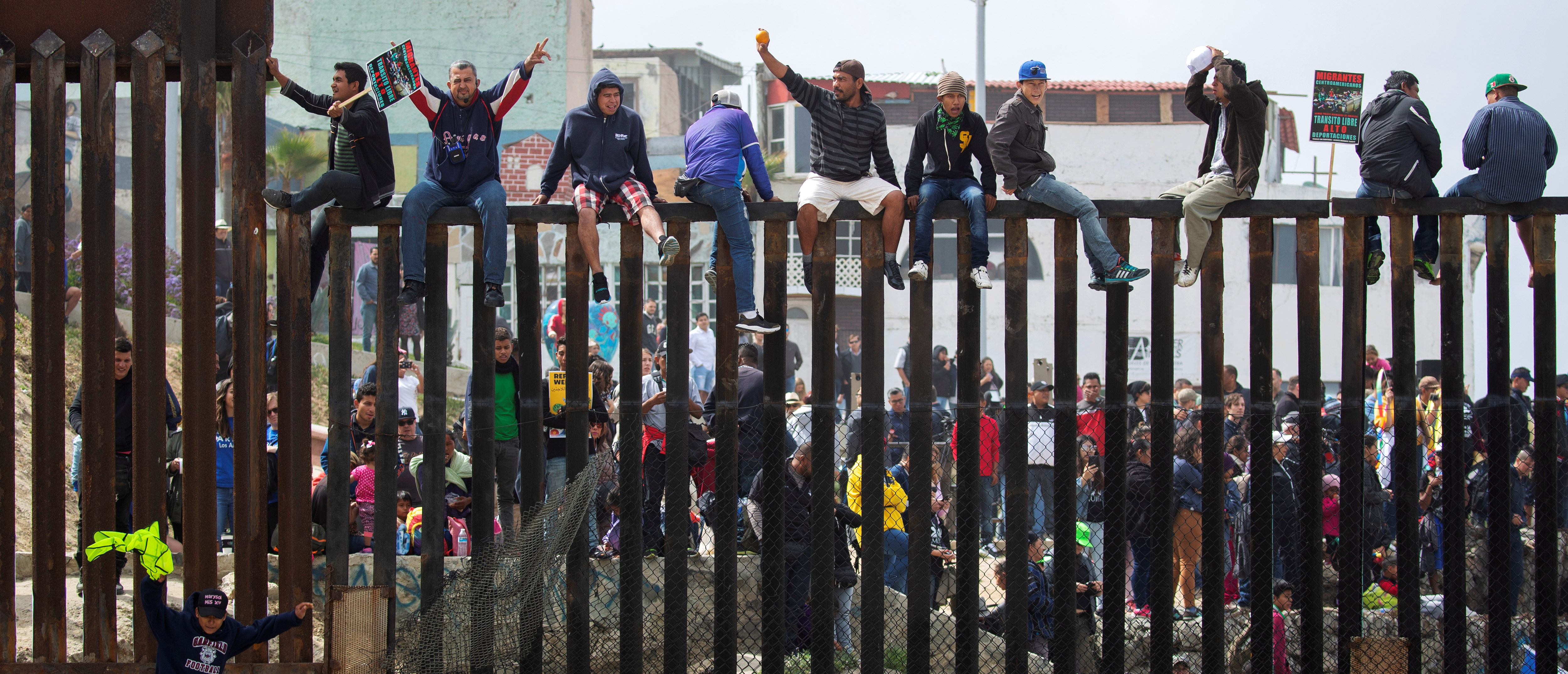 People in Mexico climb the border wall fence as a caravan of migrants and supporters reached the United States-Mexico border near San Diego, California, U.S., April 29, 2018. REUTERS/Mike Blake
