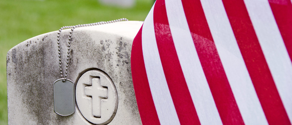 Military dog tags and American flag on veterans grave [Shutterstock/Maria Dryfhout]