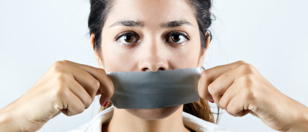 Young woman with mouth covered with tape. Concept of forbidden opinion (Josep Suria/Shutterstock)