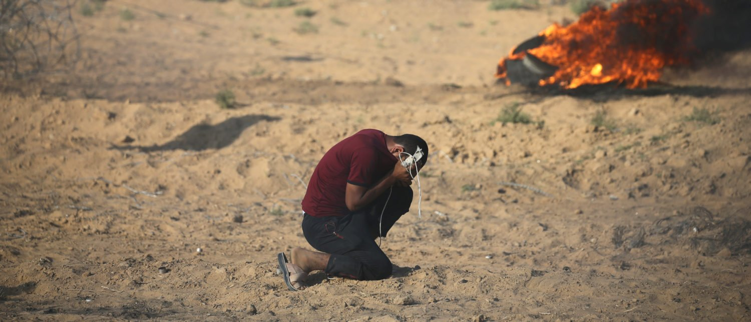 A Palestinian reacts to tear gas fired by Israeli troops during a protest at the Israel-Gaza border in the southern Gaza Strip July 13, 2018. REUTERS/Ibraheem Abu Mustafa