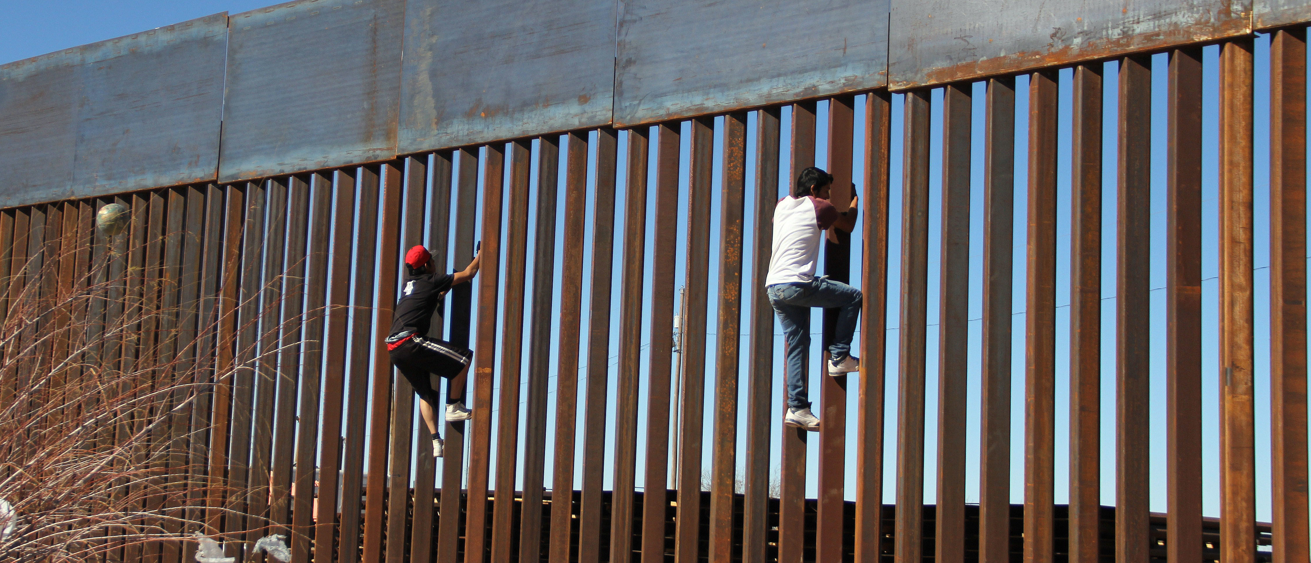 "TOPSHOT - Boys play around, climbing the border division between Mexico and the US in Ciudad Juarez, Mexico on January 26, 2017. US President Donald Trump on Thursday told Mexico's president to cancel an upcoming visit to Washington if he is unwilling to foot the bill for a border wall. Escalating a cross border war of words, Trump took to Twitter to publicly upbraid Enrique Pena Nieto. ""If Mexico is unwilling to pay for the badly needed wall, then it would be better to cancel the upcoming meeting."" / AFP / HERIKA MARTINEZ (Photo credit should read HERIKA MARTINEZ/AFP/Getty Images)"