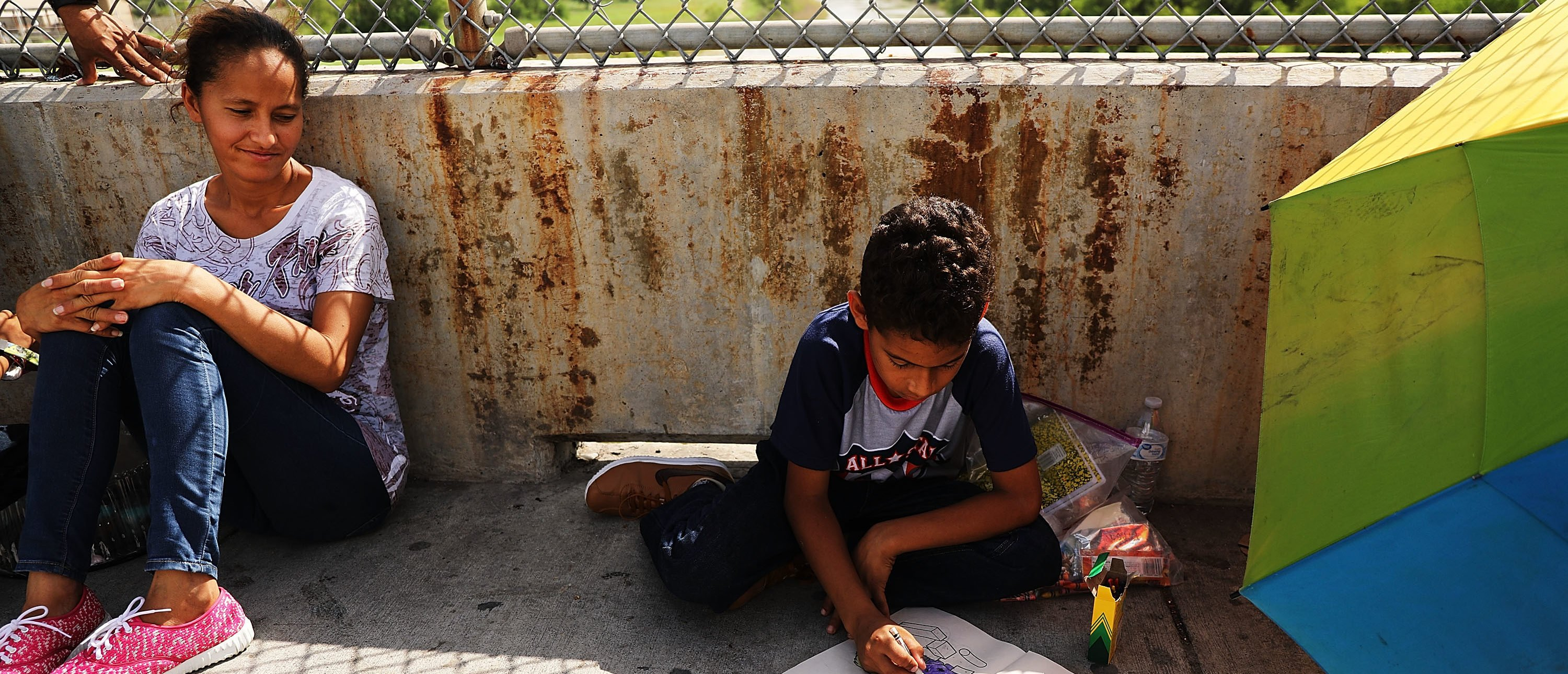 BROWNSVILLE, TX - JUNE 25: A Honduran child works in a coloring book while waiting with his family along the border bridge after being denied entry into the U.S. from Mexico on June 25, 2018 in Brownsville, Texas. Immigration has once again been put in the spotlight as Democrats and Republicans spar over the detention of children and families seeking asylum at the border. Before President Donald Trump signed an executive order last week that halts the practice of separating families who are seeking asylum, more than 2,300 immigrant children had been separated from their parents in the zero-tolerance policy for border crossers. (Photo by Spencer Platt/Getty Images)