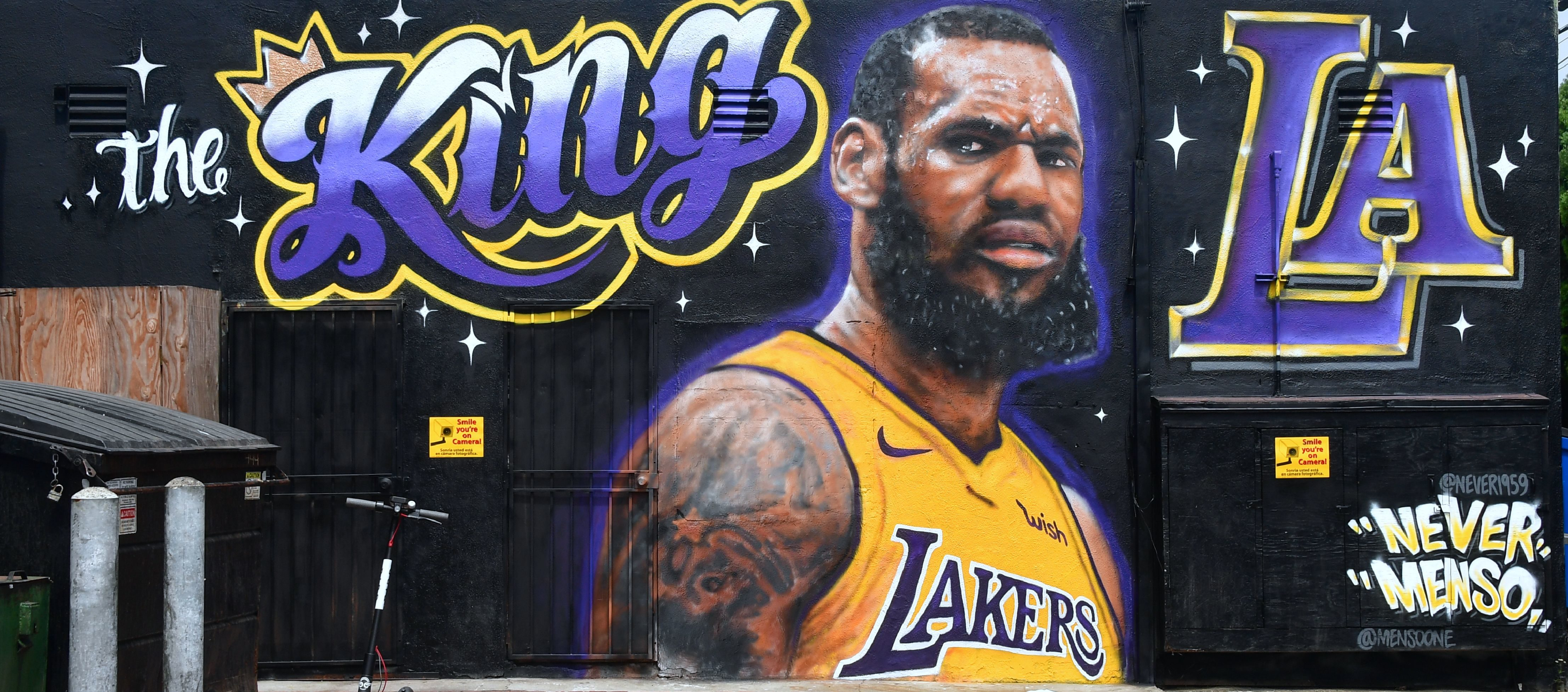 "A mural of LeBron James in a Los Angeles Lakers jersey is viewed in Venice, California on July 9, 2018. - It was originally revealed July 6, 2018, and then vandalized over the weekend, and re-touched up again with the word ""of"" not repainted from the original words ""the King of LA"". Artists Jonas Never and Menso One painted the mural to welcome LeBron James to Los Angeles, outside the Baby Blues BBQ resturant in Venice, California. (Photo by Frederic J. BROWN / AFP)"