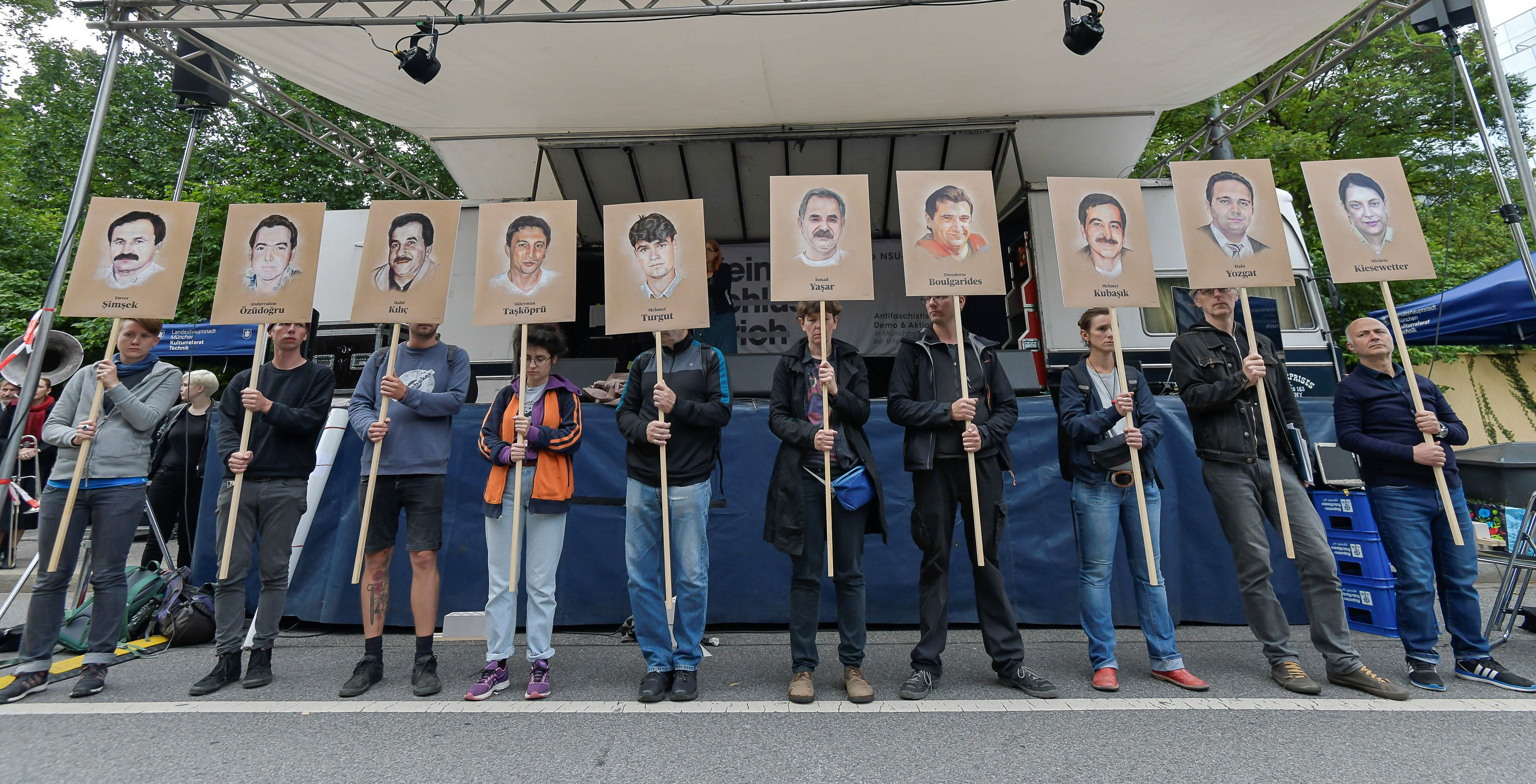 Protesters hold up signs with pictures of the victims of neo-Nazi cell National Socialist Underground (NSU) before the proclamation of sentence in the trial against Beate Zschaepe, the only surviving member of the NSU behind a string of racist murders, in Munich, Germany, on July 11, 2018. - Zschaepe, 43, is accused of complicity in 10 deadly shootings of mostly Turkish and Greek-born immigrants carried out by clandestine trio the National Socialist Underground (NSU). (Photo by Gunter SCHIFFMANN / AFP) (Photo credit should read GUNTER SCHIFFMANN/AFP/Getty Images)