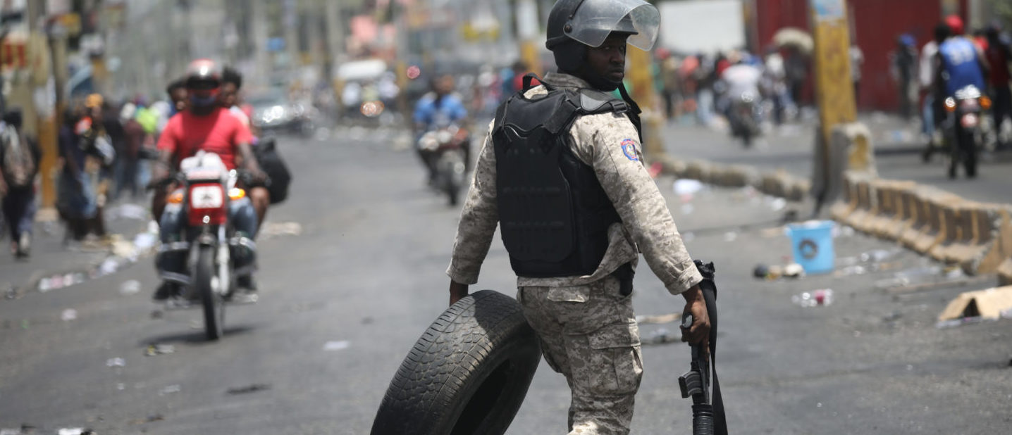 A Haitian National Police officer removes a tire from a barricade on a street in Port-au-Prince, Haiti, July 8, 2018. REUTERS/Andres Martinez Casares