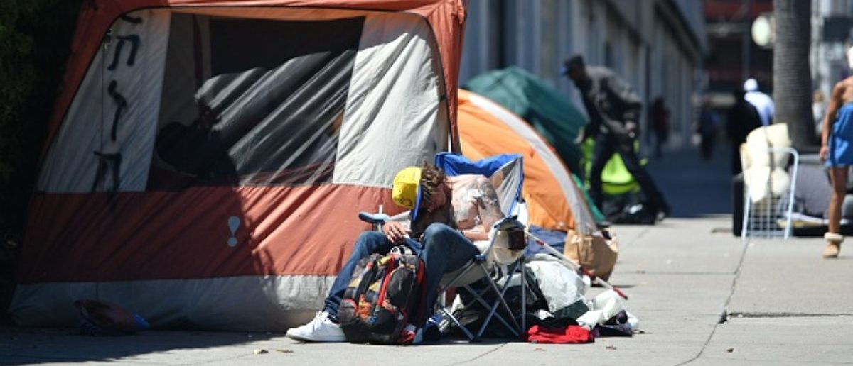 A homeless man sleeps in front of his tent along Van Ness Avenue in downtown San Francisco, California on June, 27, 2016. Homelessness is on the rise in the city irking residents and bringing the problem under a spotlight. (Photo: JOSH EDELSON/AFP/Getty Images)