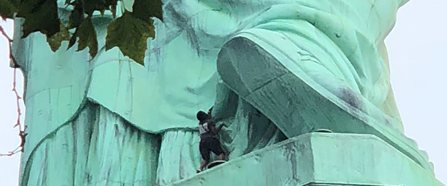 A protester is seen on the Statue of Liberty in New York, New York, U.S., July 4, 2018 in this picture obtained from social media. Danny Owens/via REUTERS
