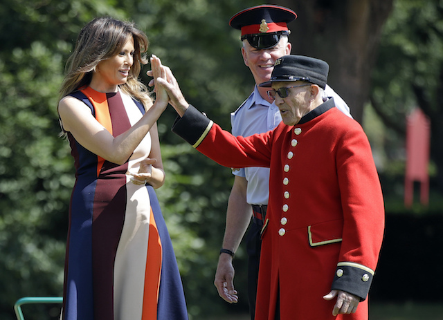 """First Lady Melania Trump high-fives with a British military veteran known as a """"Chelsea Pensioner"""" during a game of bowls at Royal Hospital Chelsea on July 13, 2018 in London, England. America's First Lady visited the Chelsea Pensioners while her husband, President Donald Trump, held bi-lateral talks with Theresa May at the Prime Minister's Country Residence. The Chelsea Pensioners are British Army personnel who are cared for at at the Services retirement home at The Royal Hospital in London. (Photo by Luca Bruno - WPA Pool/Getty Images)"""