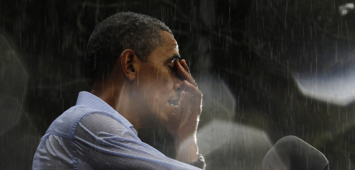 U.S. President Barack Obama wipes water off his face during a rain shower at a campaign rally in Glen Allen, Virginia, July 14, 2012. Obama travelled to Virginia on Saturday for campaign events. Rain drops on the lens created the highlights in the image. REUTERS/Jason Reed